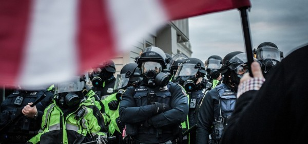 Riot police stand in the way of peaceful marches wearing military gear